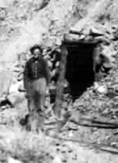 Jim Wheelock standing by tunnel at his Connor Creek mine in 1930's